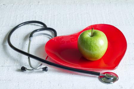 habitos saludables: Estetoscopio y una dieta placa concepto corazón rojo en pizarras blancas Foto de archivo