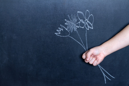 female teacher: Flowers and childs hand abstract background concept