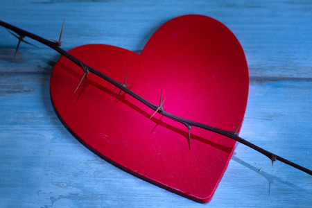 heart pain: Red wooden valentines heart and thorn abstract pain concept Stock Photo