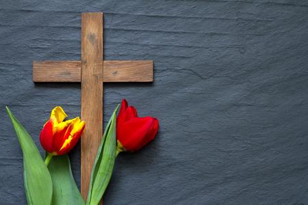 resurrección: tulipanes de Pascua abstractos y cruz de madera en el mármol negro Foto de archivo