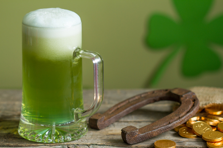 good time: St. Patricks Day green beer and horseshoe abstract background