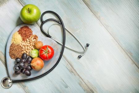 stile di vita e concetto di assistenza sanitaria sano con il cibo, il cuore e stetoscopio