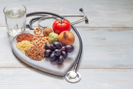 Healthy lifestyle and healthcare concept with food, heart and stethoscope