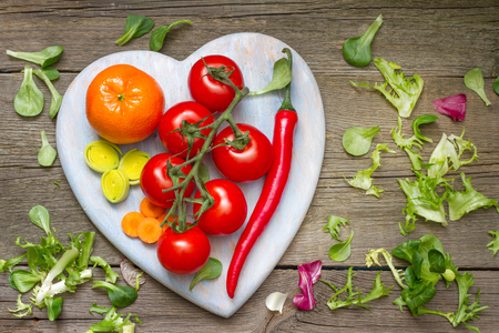 rapunzel: Fresh spring vegetables on wooden heart health lifestyle diet concept