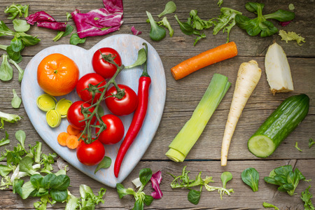 Fresh spring vegetables on wooden heart health lifestyle diet concept