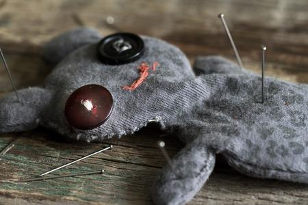 vodoo: Voodoo doll and pins on old vintage wooden floor
