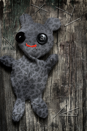 vodoo: Voodoo doll and pins on old vintage wooden floor