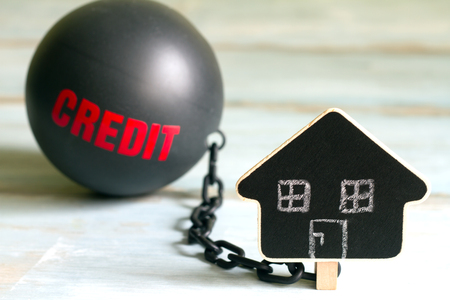 housing loan: Slave housing loan concept with credit iron ball and house symbol Stock Photo