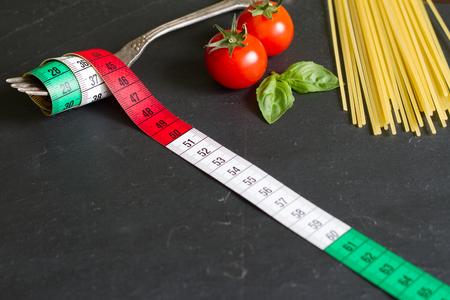 Spaghetti-Food-Konzept mit Zentimeter auf Gabel italienischer Flagge und Pasta Standard-Bild