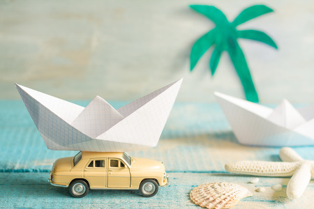 Holiday vacation concept with abstract origami boat and tropical beach
