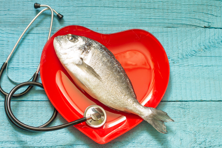 doctor fish: Fish on red heart plate and stethoscope cardiology diet concept