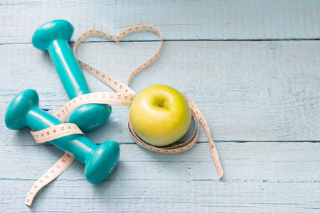 Fitness and diet abstract concept with dumbbells