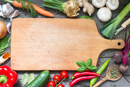 Spice herbs and vegetables frame food background and empty cutting board Foto de archivo