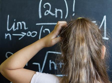 Schoolgirl thinks on the difficult task of mathematics on blackboard photo
