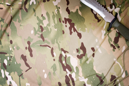 matchmaker: Combat knife on military camouflage fabric background concept