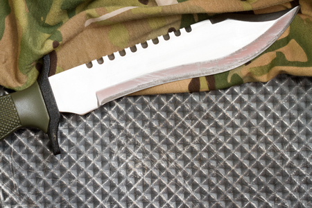 matchmaker: Combat knife on military camouflage fabric and metal background concept Stock Photo