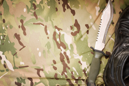 matchmaker: Combat knife and shoes on military camouflage fabric background