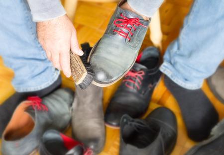personal de limpieza: Un hombre limpia los zapatos con un cepillo, limpiabotas Foto de archivo