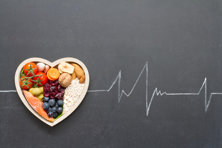 cardiograph: Healthy food in heart and cardiograph on blackboard medical abstract concept