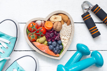 Food in heart and dumbbells fitness abstract healthy lifestyle concept Standard-Bild