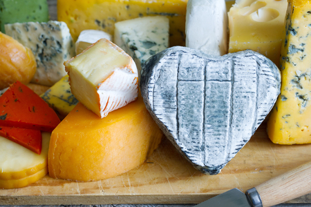 food still: Heart shaped cheese on old boards colorful food abstract still life Stock Photo