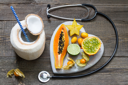 Tropical diet concept with heart coconut milk and stethoscope