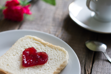 Breakfast with heart shape jam on the bread abstract concept still life