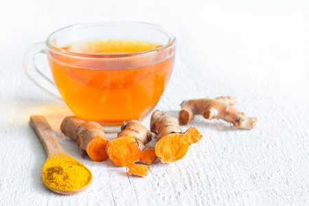 Raw roots of tumeric and tea on white planks detox concept
