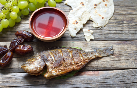 Easter food with fish passover bread cross in goblet of wine last supper abstract Stock Photo