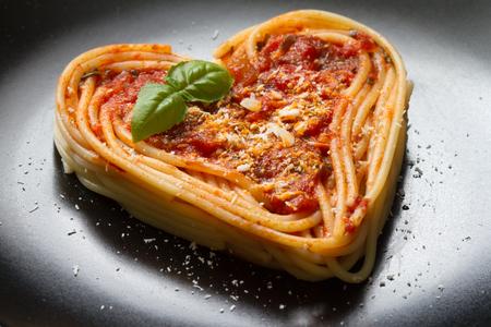 Spaghetti pasta heart love italian food diet concept on black background Stock Photo - 95671939