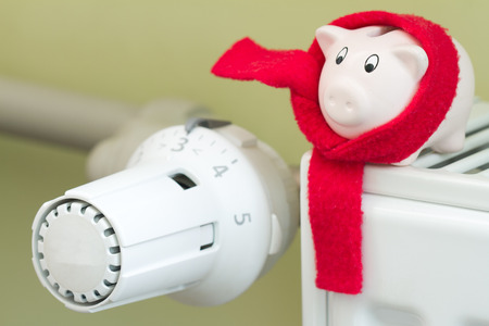 Save money concept with thermostat and piggybank on green background