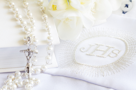 First holy communion symbol concept with rosary and flowers