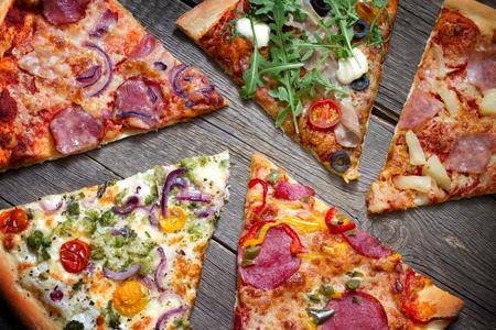 Pezzi di pizza di diversi tipi su vecchie tavole retrò still life concept Archivio Fotografico