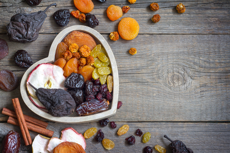 Dried fruits on wooden board in the heart food concept Stock Photo