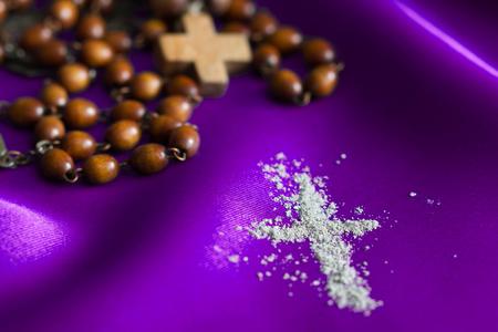 Concepto de religión del miércoles de ceniza sobre fondo de tela violeta con rosario