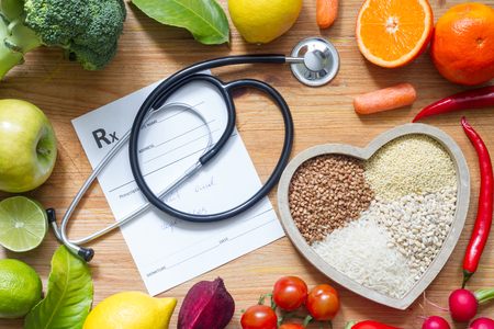 Healthy lifestyle with food in heart and stethoscope. Alternative medicine concept