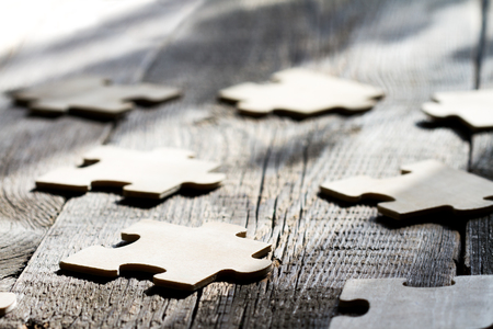 Teamwork in business concept with puzzle on wooden board