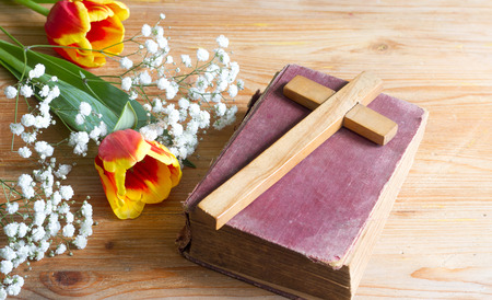Spring easter flowers and cross on wooden background