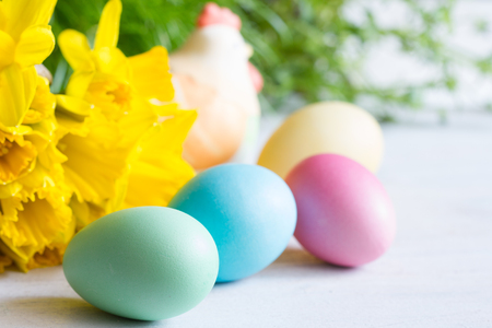 Spring daffodils and colorful easter eggs on blurred background