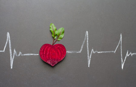 Healthy beetroot with heart shape and electrocardiogram on blackboard Stockfoto