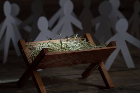 Jesus came to all people. Birth of Jesus with manger and paper people abstract christmas symbol Imagens