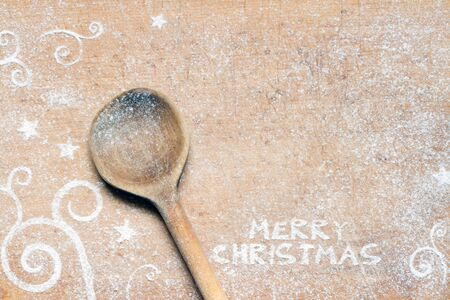 Christmas food background with spoon and flour. Merry Christmas inscription Stock Photo