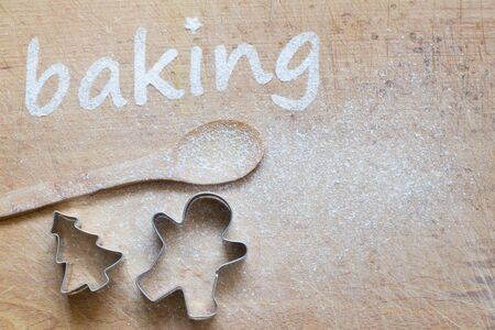 Christmas background with cookies molds, spoon and sweet decoration. Baking text made with flour