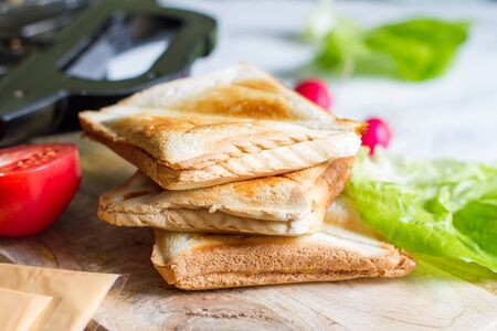 Toast with toaster sandwich maker breakfast concept and ingredients