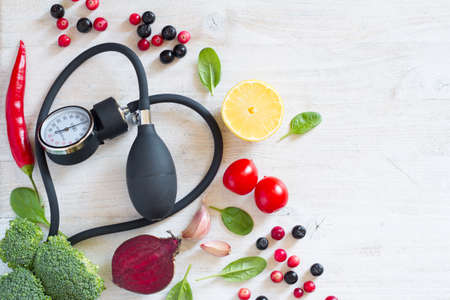 Heart-shaped blood pressure monitor and vegetables with fruits to prevent hypertension, healthy diet concept