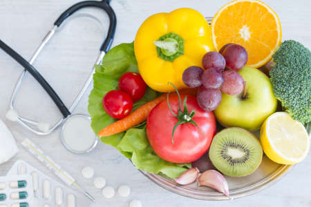 Fruits and vegetables platter, medications in background. Healthy diet alternative Standard-Bild