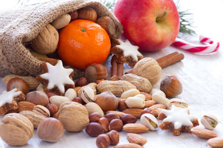 Nuts, fruits and cookies in jute sack, natural christmas food background Standard-Bild
