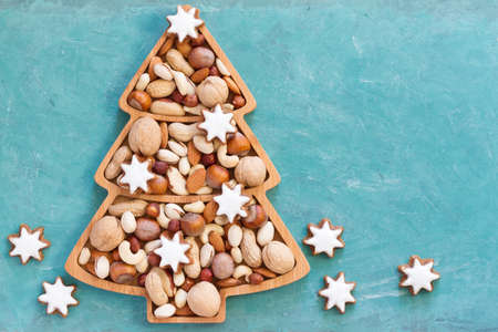 Nuts and cookies in Christmas tree-shaped bowl on blue background