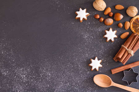 Christmas background with flour, cookies, nuts and spices