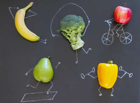 Healthy lifestyle, fitness concept. Fruits and vegetables workout on blackboard, abstract